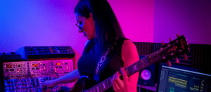 Music artist Nina Richards standing between an electronic keyboard and a synthesizer, bolding an electronic guitar and holding a guitar pick with their mouth.