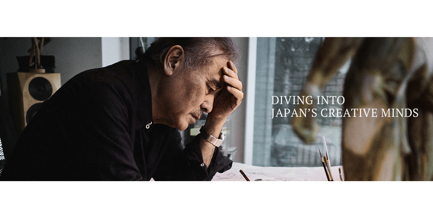 Photo of a graying Japanese man seated at a desk, focusing intently on something he's working on with a pencil