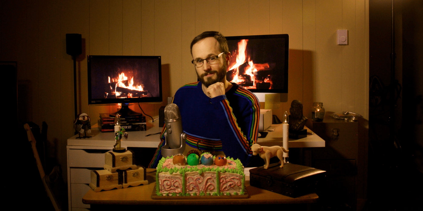 Photo of Matt Baume seated at a table with his chin resting on his fist, looking directly at the camera.
