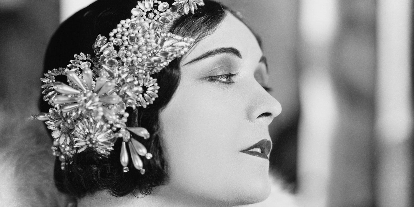 Still photo from a black and white silent film, a young women wearing a glamorous beaded headband, looking wistfully to her left.