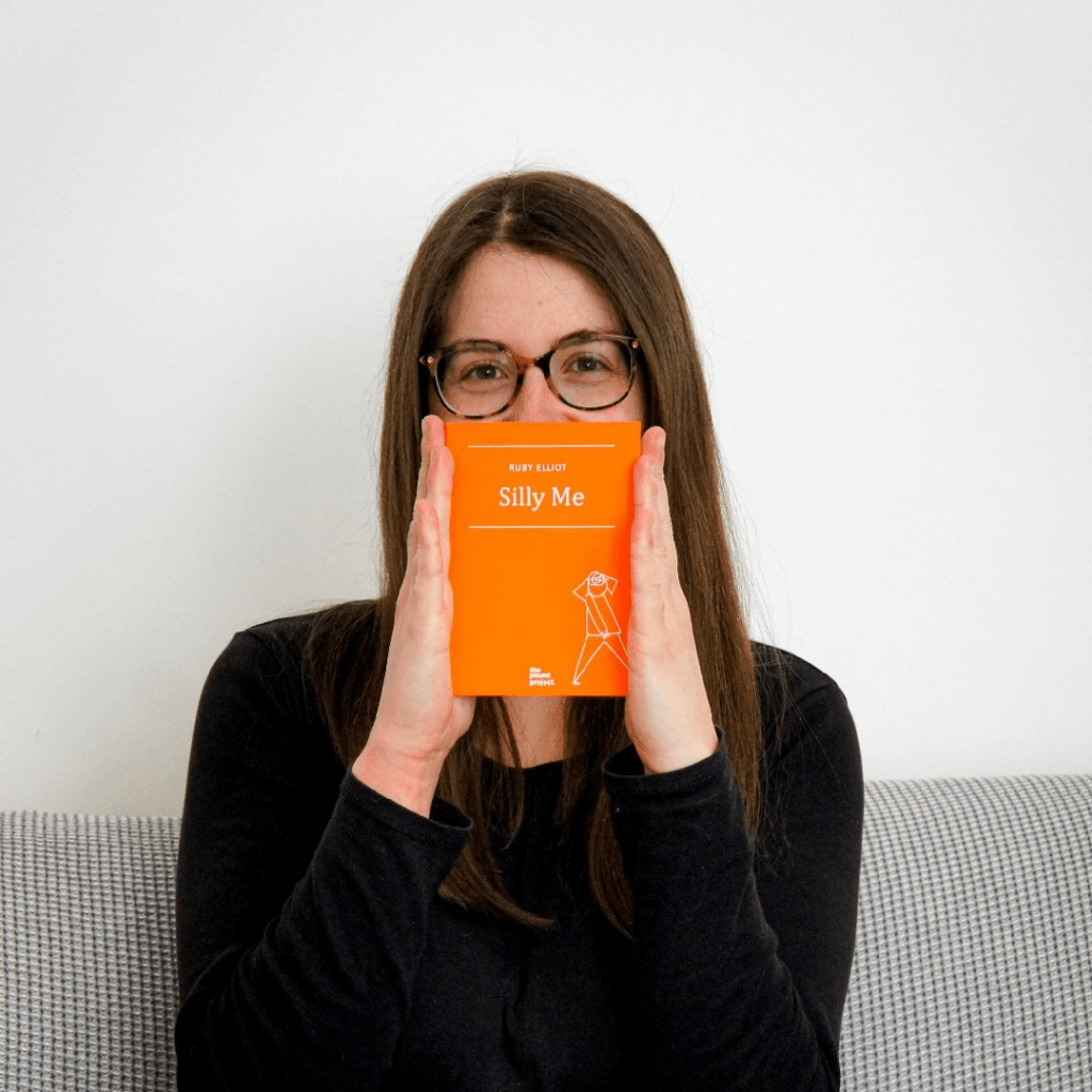"""Photo of Ruby Elliot, cartoonist, holding a copy of her book, """"Silly Me"""" in front of her face so that it covers her nose and mouth. She's wearing round-ish horn rimmed glasses and has long straight medium brown hair."""