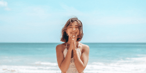 ediyasmr - photo of Ediya Daulet standing on the beach, the waves in the background, her hands in a prayer pose in front of her chin, smiling